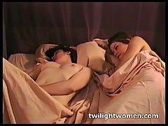 Две голые брюнетки сладко ласкают киски на кровати.